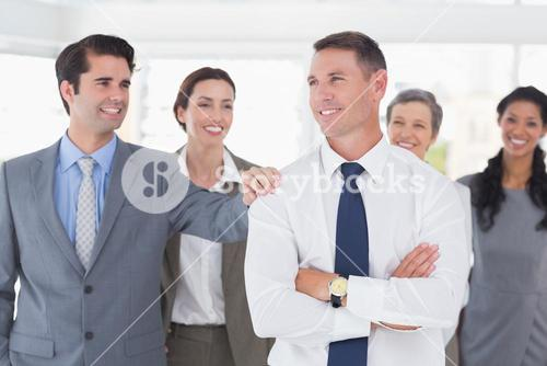 Business people congratulating their colleague