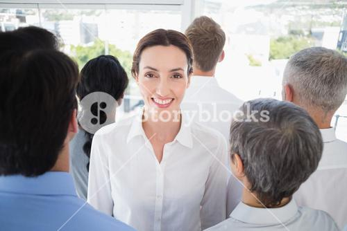 Smiling businesswoman with colleagues back to camera