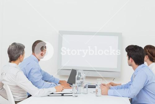 Business team looking at white screen