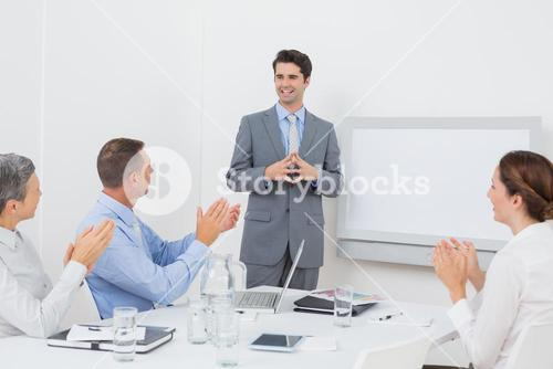 Business team applauding their colleague