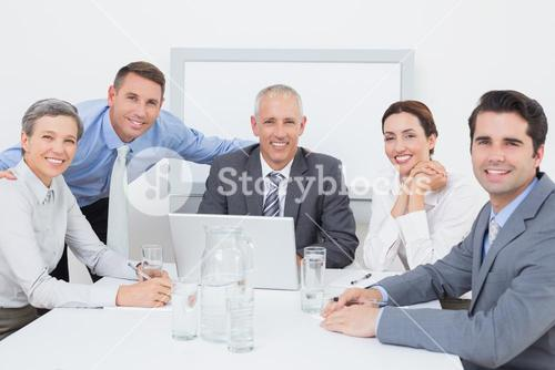 Business team working happily together on laptop