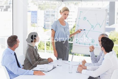 Businesswoman explaining the graph on the whiteboard