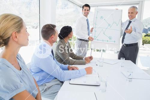 Businessmen explaining the graph on the whiteboard