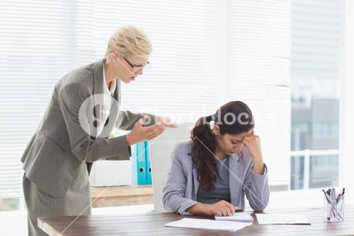 Businesswoman giving orders at her coworker