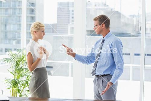 Businessman giving out to his colleague