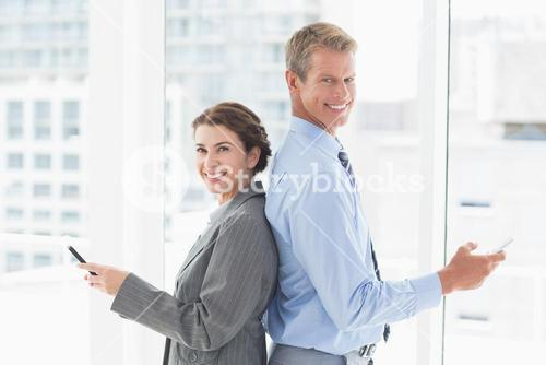 Smiling businesswoman back-to-back with colleague