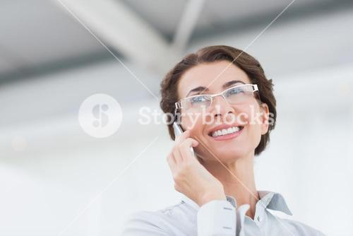 Smiling businesswoman on the phone wearing eye glasses