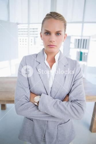 Unhappy businesswoman looking at camera with arms crossed