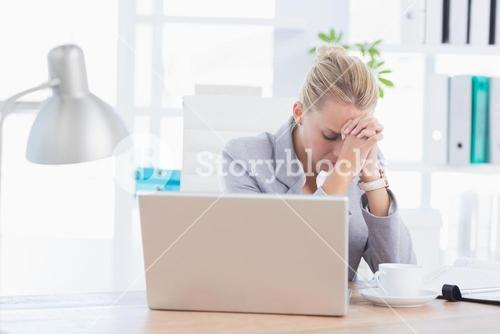 Frustrated businesswoman with head in hands