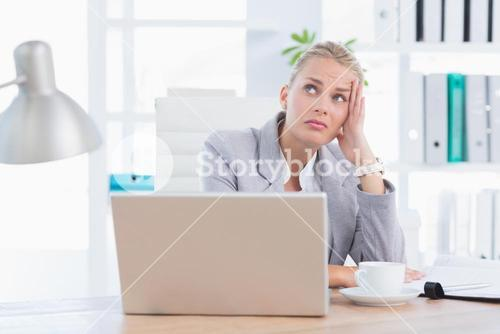 Frustrated businesswoman with head in hand