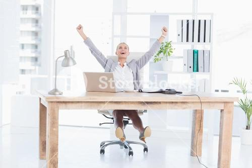 Happy businesswoman with raised arms