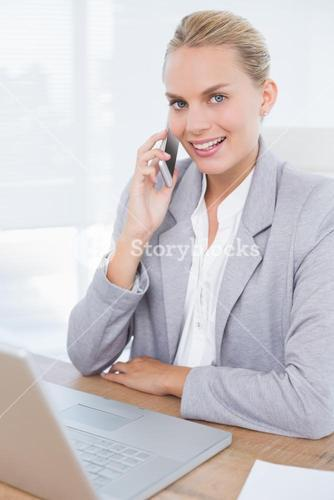 Smiling businesswoman phoning at her desk