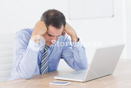 Frustrated businessman working with his computer