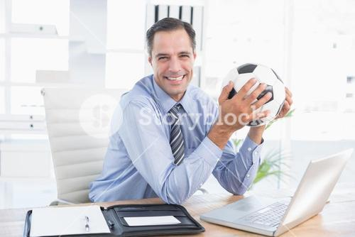 Smiling businessman looking at camera with foot ball