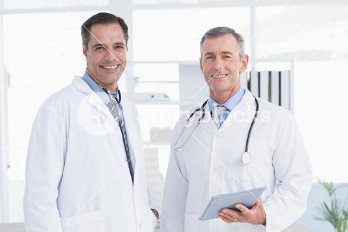 Doctor and his colleague looking at camera