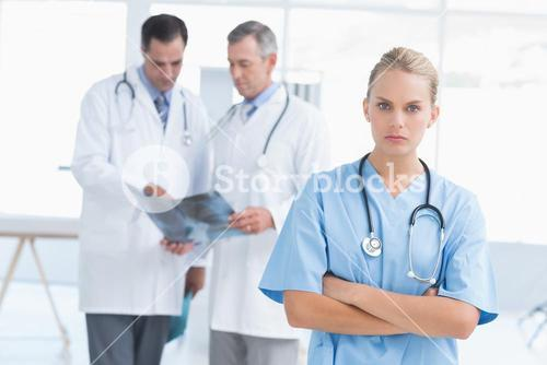Irritated doctor looking at camera while her colleagues works
