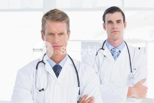 Unsmiling doctors looking at camera with arms crossed