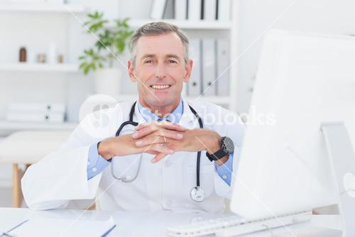 Smiling doctor looking at camera with hands crossed