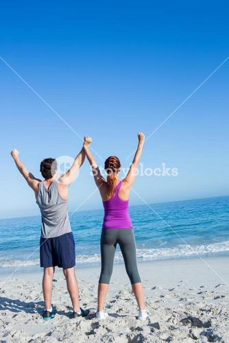 Happy couple raising their hands