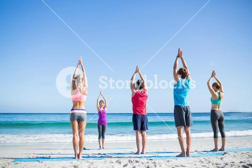 Friends doing yoga together with their teacher