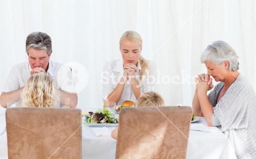Pretty family praying at the table