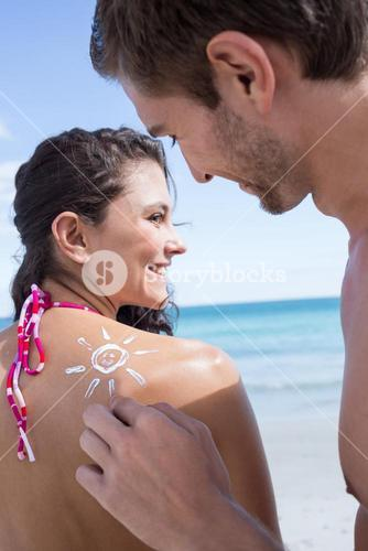 Handsome man putting sun tan lotion on his girlfriend