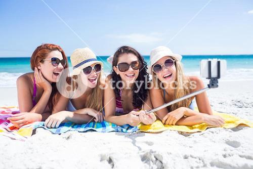 Happy friends wearing sun glasses and taking selfie
