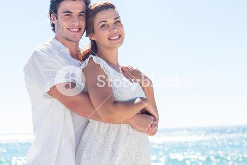 Happy couple hugging and looking at camera