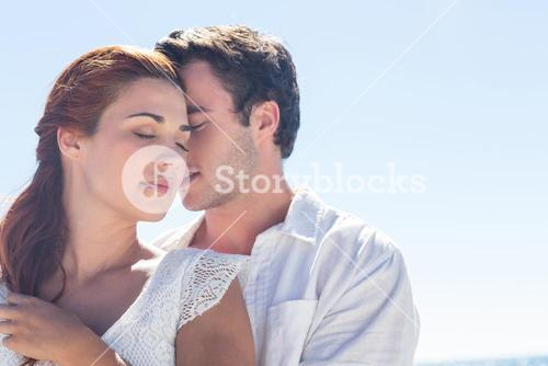 Happy couple hugging eyes closed