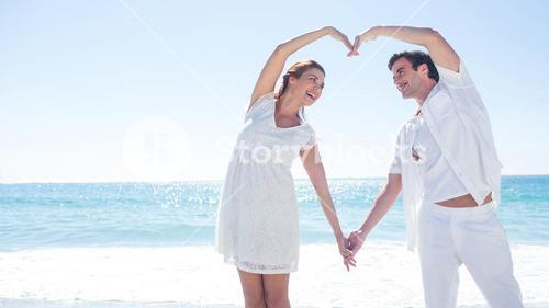 Happy couple forming heart shape with their hands