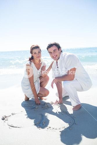 Happy couple drawing heart shape in the sand
