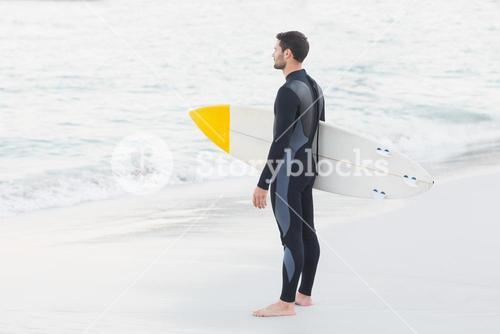 Man in wetsuit with a surfboard on a sunny day