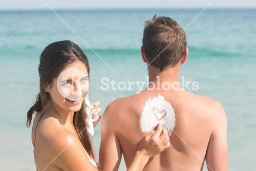 Woman putting sun tan lotion on her boyfriend