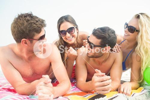 group of friends in swimsuits speaking together