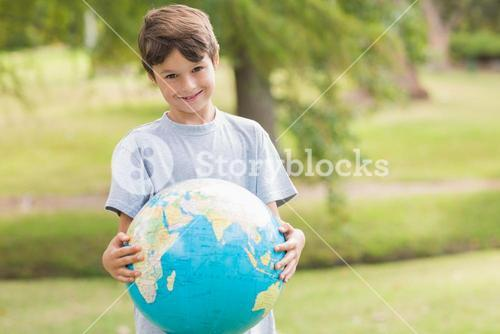 Smiling boy holding an earth globe in the park