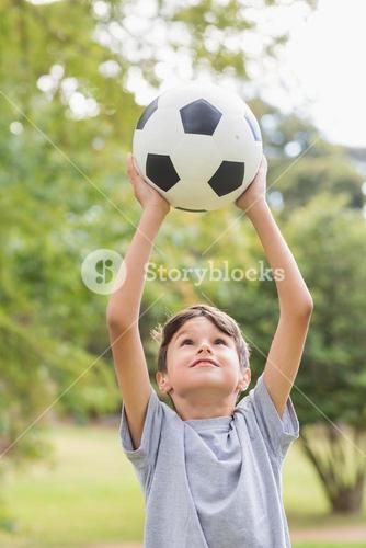 Boy holding a soccer ball in the park