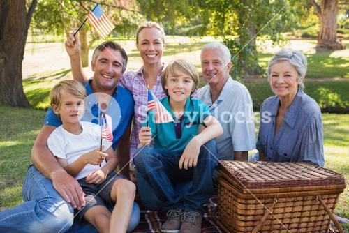 Happy family in the park and holding american flag