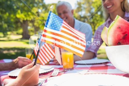 Happy family having picnic and holding american flag