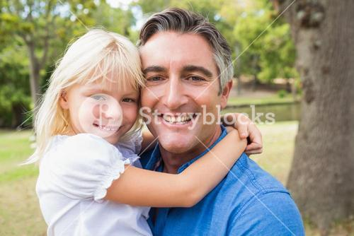 Happy father smiling at camera with his daughter