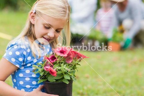 Young girl sitting with flower pot
