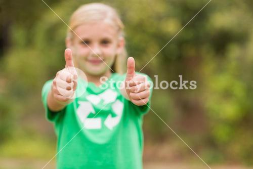 Happy little girl in green with thumbs up