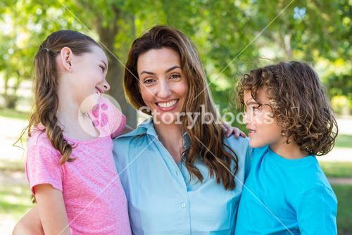mother and children smiling and kissing in a park