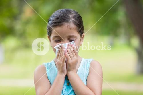 Little girl blowing his nose