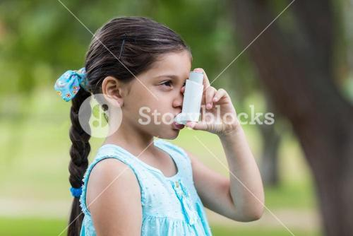 Little girl using his inhaler