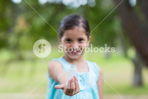 Little girl showing his inhaler
