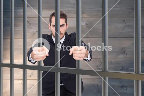 Composite image of angry businessman standing with clenched fists