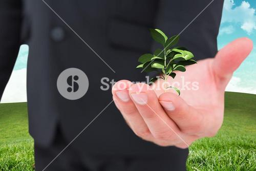 Composite image of businessman holding out his hand