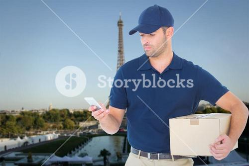 Composite image of delivery man using mobile phone while holding package