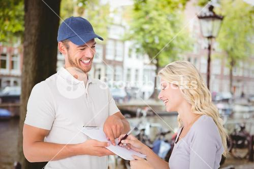 Composite image of happy delivery man getting signature from customer