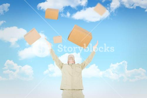 Composite image of excited delivery man with arms raised looking up